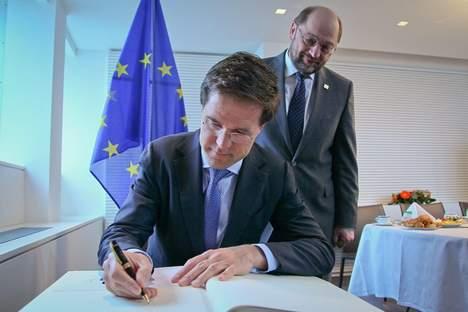Rutte looking at a pen