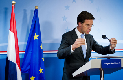 Mark Rutte looking at a microphone