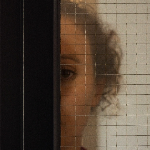 Portrait from a girl standing behind security glass III