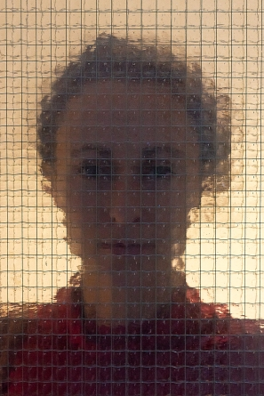 Portrait from a girl standing behind security glass I